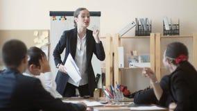 Bizneswomanu aktywnie gestykuluje, głośni klęcie, i bardzo nieszczęśliwy z pracą ich podwładni zbiory
