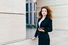 Bizneswomanu być ubranym formalny odziewa, trzymający nowożytnego gadżet który używa dla czytelniczych wiadomości, emaili lub inf obrazy stock