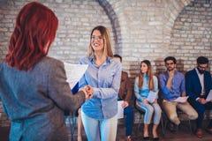 Bizneswomanu chwiania ręki z kobietą oprócz ludzi czeka akcydensowego wywiad Obraz Royalty Free