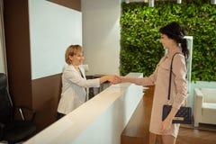 Bizneswomanu chwiania uśmiechnięta ręka administrator przy kliniką obrazy royalty free