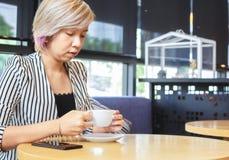 Bizneswomanu chwyta filiżanka kawy w sklep z kawą obrazy stock