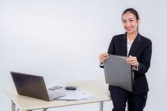 bizneswomanu chwyta kartoteki dokumentu przyglądająca kamera z obsiadanie stołem Fotografia Royalty Free