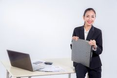 bizneswomanu chwyta kartoteki dokumentu przyglądająca kamera z obsiadanie stołem w biurze na białym tle Obraz Stock