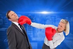 Bizneswomanu ciupnięcia kolega z jej bokserskimi rękawiczkami Fotografia Stock