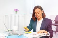 Bizneswomanu cyrklowania rachunki używać mądrze telefon zdjęcia royalty free