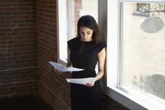 Bizneswomanu czytania dokumentu pozycja Biurowym okno Zdjęcie Stock