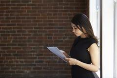 Bizneswomanu czytania dokumentu pozycja Biurowym okno Zdjęcia Royalty Free