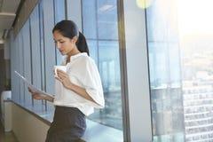 Bizneswomanu czytania dokumentu pozycja okno Obrazy Royalty Free