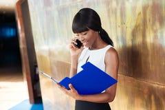 Bizneswomanu czytanie tapetuje i opowiadający na telefonie Fotografia Royalty Free