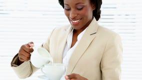 Bizneswomanu dolewania mleko w jej filiżankę zbiory