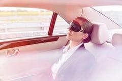 Bizneswomanu drzemanie z mask? w samochodzie podczas podr??y zdjęcie stock