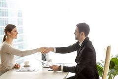 Bizneswomanu handshaking z biznesmenem przy biurkiem fotografia stock