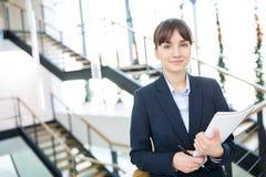 Bizneswomanu mienia dokumenty Podczas gdy Stojący Przeciw schodom obraz stock