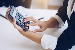 Bizneswomanu mienia kalkulator dla kalkuluje liczbę i dyska zdjęcia stock