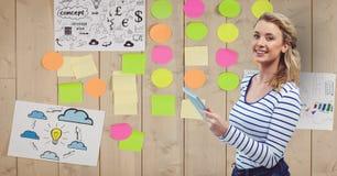 Bizneswomanu mienia pastylki pecet z adhezyjnymi notatkami wtykał na ścianie Zdjęcia Stock