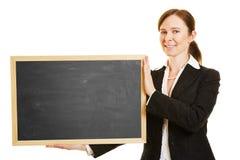 Bizneswomanu mienia pusty blackboard Zdjęcie Stock