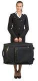 Bizneswomanu mienia walizka, patrzeje kamerę Obraz Stock
