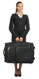 Bizneswomanu mienia walizka, patrzeje kamerę Zdjęcia Royalty Free