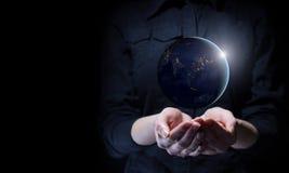 Bizneswomanu mienia ziemi planeta w palmie Fotografia Royalty Free