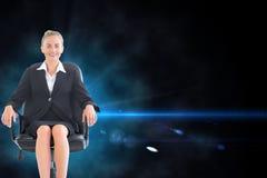 Bizneswomanu obsiadanie na swivel krześle w czarnym kostiumu Obrazy Stock