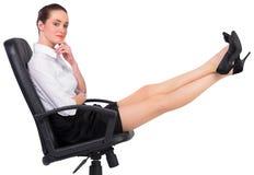 Bizneswomanu obsiadanie na swivel krześle z ciekami up Zdjęcia Royalty Free