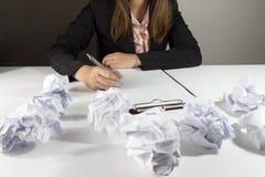 Bizneswomanu obsiadanie przy jej biurkiem z błędu życiorysem Zdjęcie Stock