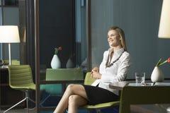 Bizneswomanu obsiadanie W Biurowym I Uśmiechniętym Fotografia Stock