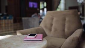 Bizneswomanu obsiadanie w karle w hotelu kuluarowym opowiada telefonie komórkowym, pisać w notepad i używać laptop zdjęcie wideo