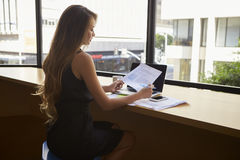 Bizneswomanu obsiadanie w nowożytnym biurowym czytaniu dokument fotografia stock