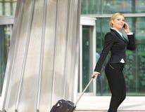 Bizneswomanu odprowadzenie z walizką i opowiadać na telefonie komórkowym Zdjęcia Stock