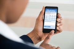 Bizneswomanu plombowania ankiety forma Na telefonie komórkowym obrazy stock