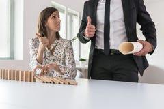 Bizneswomanu powstrzymywania spada domina i pokazywać aprobaty podpisują fotografia royalty free
