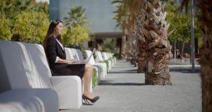 Bizneswomanu siedzący działanie w miastowym parku zbiory
