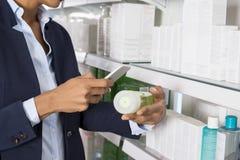 Bizneswomanu skanerowania produktu ` s Barcode Przez Mądrze telefonu Zdjęcie Stock