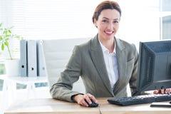 Bizneswomanu używać komputerowy i ono uśmiecha się przy kamerą Obraz Royalty Free
