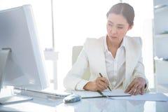 Bizneswomanu writing na dzienniczku na biurku Obrazy Royalty Free