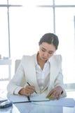 Bizneswomanu writing na dzienniczku na biurku Zdjęcie Stock