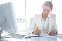 Bizneswomanu writing na dzienniczku na biurku Fotografia Stock