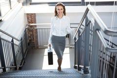 Bizneswomanu wspinaczkowy schody w biurze Obraz Stock