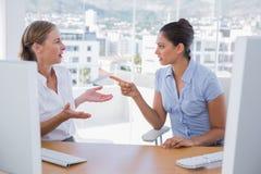 Bizneswomany dyskutuje przy ich biurkiem Obraz Royalty Free