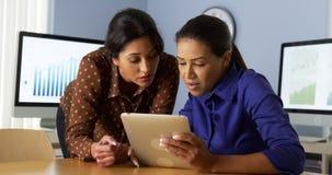 Bizneswomany pracuje na pastylka komputerze z latynoskim kolegą zdjęcie royalty free