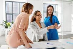 Bizneswomany z smartphone pracuje przy biurem zdjęcia royalty free