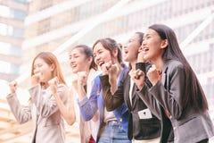 Bizneswomany zespalają się sukcesu osiągnięcie z ręką podnoszącą zdjęcie royalty free