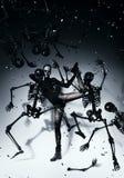 Bizzare woman dancing with skeletons. In studio Stock Image