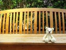 björn för amigurumivirkningnalle på den ensamma bänken Fotografering för Bildbyråer