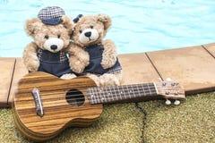 Björn för nalle som två rymmer handen med ukulelet Arkivbild
