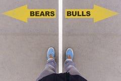 Björnar vs tjurar smsar på pilar på asfaltjordning, fot och skor arkivfoton
