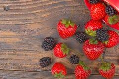 Björnbär strawberriesonträtabellbakgrund som spills från en kryddakrus Antioxidants detox bantar, organiska frukter Royaltyfri Foto
