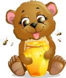 björnen äter honung Arkivbild