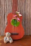 Björnen leker med ukulelet på träbakgrunder Fotografering för Bildbyråer